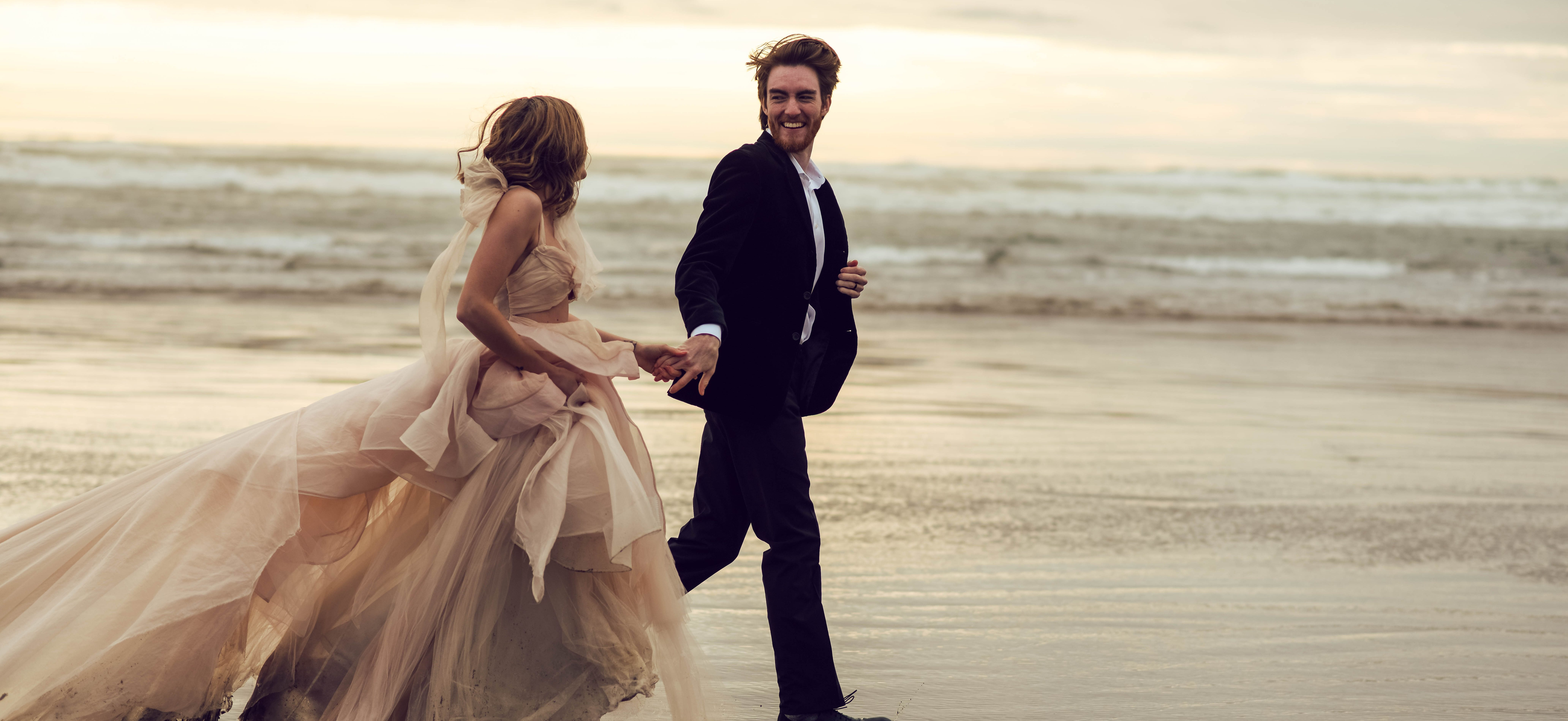 bride and groom run down a beach smiling with washington wedding photography by adina stiles