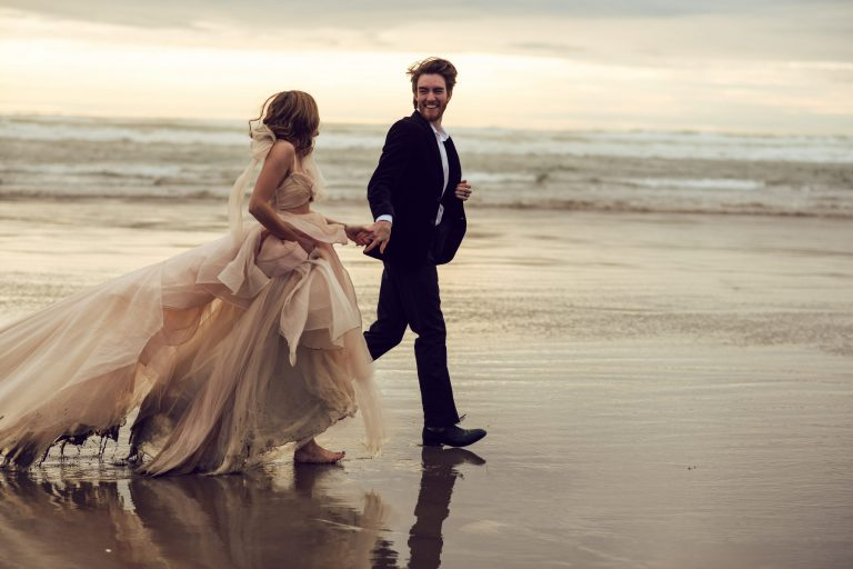 bride wearing a pink gown runs along the beach with her groom in this wedding image in the wedding portfolio of adina stiles photography