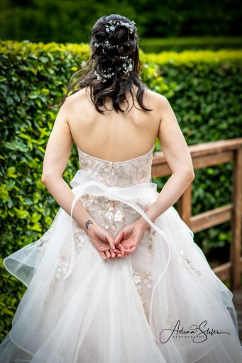 bride faces away from the camera with her hands clasped together behind her showing the back of her beautiful gown during her seattle wedding with adina stiles