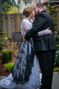 bride wearing a white lacy gown with a black lace overlay kisses her groom during their Maple Valley wedding on Leap Day 2020 in Washington with Adina Stiles