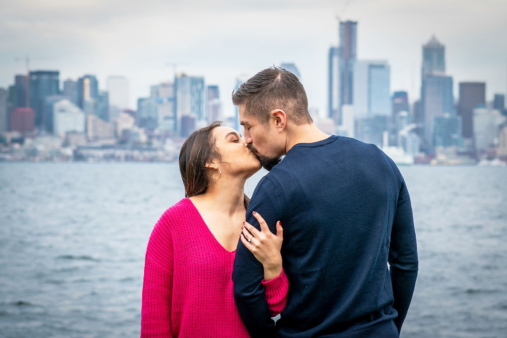 long haired young woman wearing a fuschia shirt holds on to her fiance and gives him a kiss with the city of seattle behind them getting engagement photography with Washington